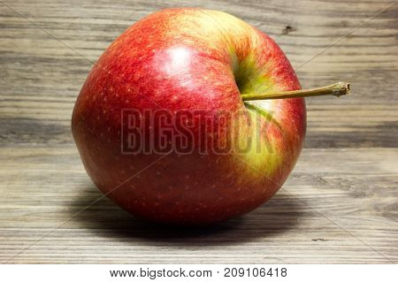 Red Apple on wooden table as background