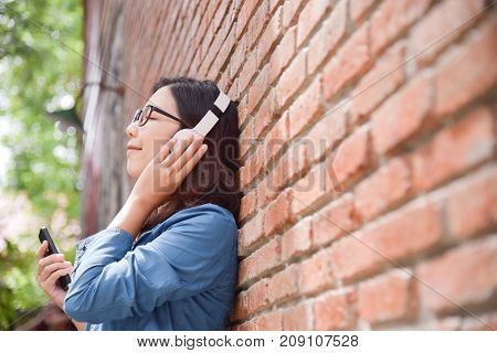 Happy Beautiful Asian woman in blue shirt listening to the music with headphone via her smart phone on old red brick wall background. copy space.