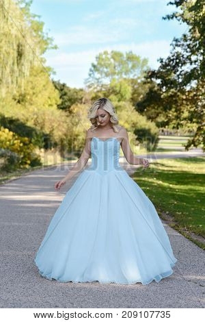 young woman in blue ball gown in garden