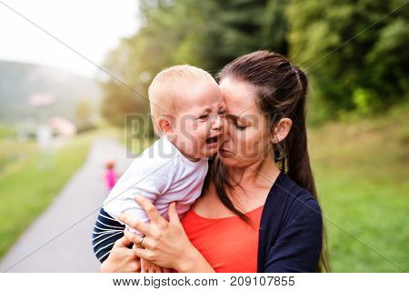 Crying little boy with his mother in nature. Young woman holding her toddler boy. Summer time.