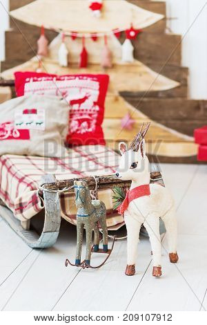 Vintage sledge with toy deer and horse. Christmas and New Year details of home interior.