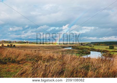 Rainbow over field and river Nerli Vladimir region Russia. Beautiful autumn landscape in sunny day after rain.