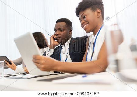 business, people and education concept - african american businessman and businesswoman with tablet pc computer at international conference
