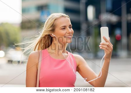 technology, lifestyle and people concept - smiling young woman with smartphone and earphones listening to music and taking selfie in city