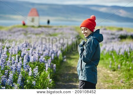 Girl in warm clothing observing surroundings on background of field of flowers and mountains of Iceland.