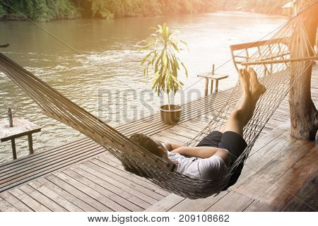 Man sleeping on the cradle in the river side