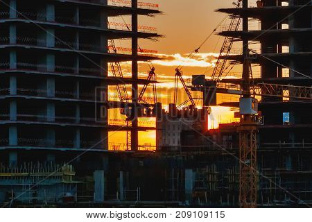 Sunset at the construction site. Silhouettes of cranes and unfinished floors on orange sky background. Moscow Russia.