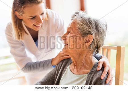 Health visitor and a senior woman during home visit. A nurse talking to an elderly woman.