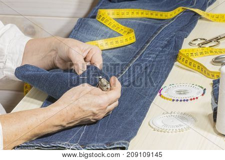 A seamstress basting the bottom of the pants