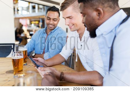 people, male friendship and technology concept - happy friends with tablet pc computer drinking beer at bar or pub