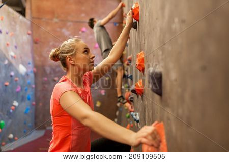 fitness, extreme sport, bouldering, people and healthy lifestyle concept - man and woman exercising at indoor climbing gym