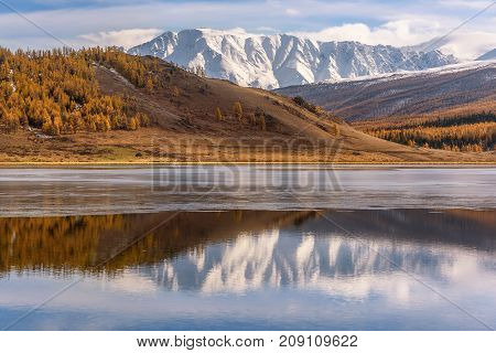 A picturesque autumn landscape with mountains covered with snow a golden forest and a beautiful lake with first thin ice and reflections on the background of blue sky and clouds
