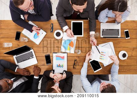 Multiethnic team meeting top view. Manager and emploees listen to the report in comfortable office, top view of wooden table