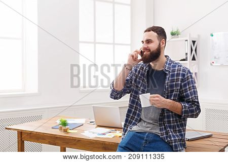 Happy and relaxed businessman in casual talk on mobile in office. Young businessman in casual has phone talk in modern workplace interior.
