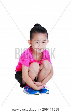 Full body of adorable asian child in sportswear smiling and looking at camera. Healthy chinese girl relaxing at studio. Isolated on white background.