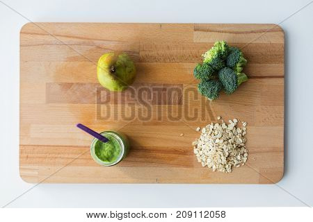 baby food, healthy eating and nutrition concept - glass jar with green vegetable puree, pear, broccoli and oatmeal on wooden cutting board