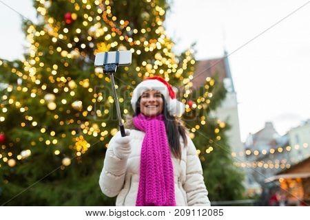 holidays, technology and people concept - happy woman taking picture with smartphone selfie stick at christmas tree at old town hall square in tallinn