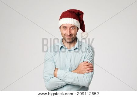 Relaxed mature man wearing santa claus hat standing with hands crossed on white background. Confident spanish male ready for Christmas holidays