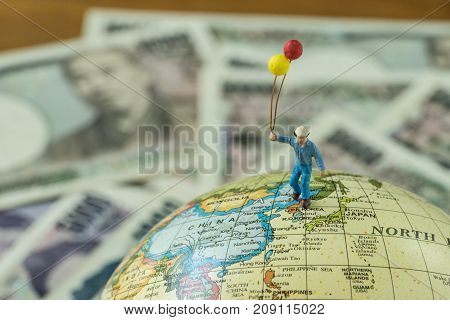 Miniature figure men holding balloons standing on north korea and japan map globe as peace and war solution concept.