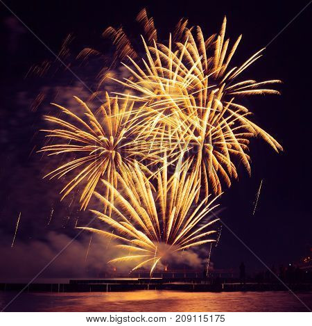 beautiful Golden fireworks over the sea on night sky background