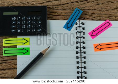 financial target concept as selective focus on pencil on white paper notebook with arrow stick paper and black calculator.
