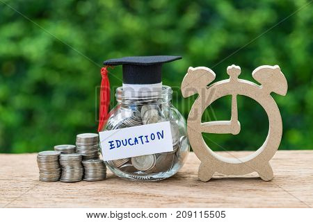 glass jar with full of coins and graduates hat labeled as Education wooden alarm clock as education or savings concept.