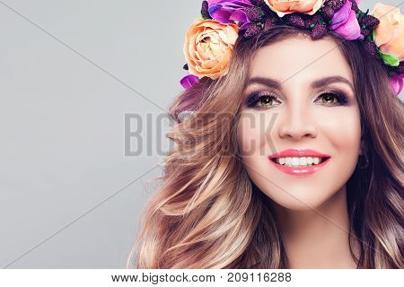 Young Beautiful Woman Smiling. Cute Model with Wavy Blonde Hair Makeup and Colorful Flowers Wreath on Gray Background with Copy space