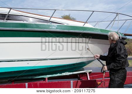 Caucasian man washing power boat hull with pressure washer