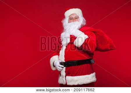 Christmas. santa claus with big bag on shoulder is on red background.
