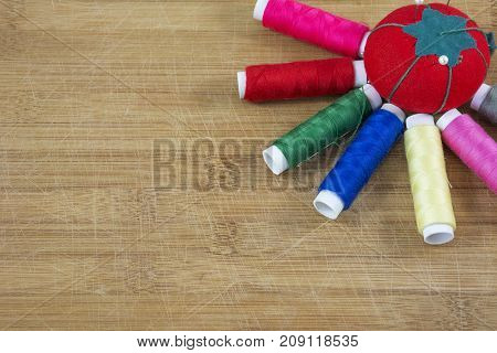 One red pincushion and several colourful threads as a sun on the light wooden background
