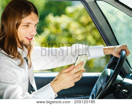 Man Using His Phone While Driving Car.