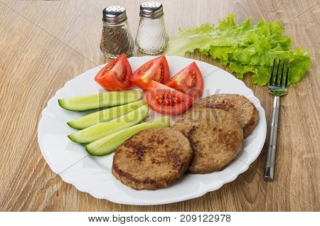 Fried Cutlets, Lettuce, Tomato, Cucumbers, Salt, Pepper And Fork On Wooden Table