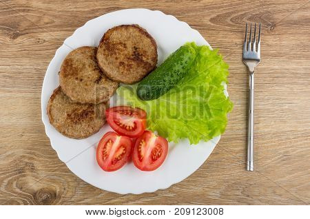Dish With Fried Cutlets, Lettuce, Tomato, Cucumbers, Fork On Table