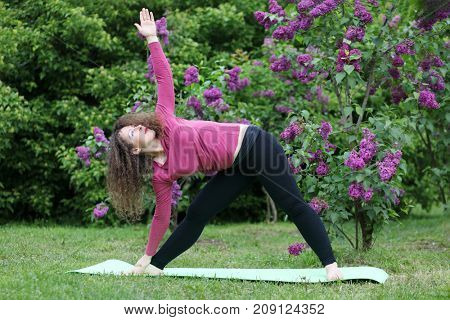 Woman does exercises on rug near bushes of blossoming lilacs at spring