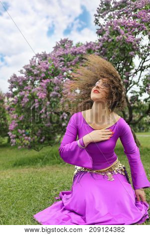 Woman in costume for belly dance sits on lawn near bushes of blossoming lilacs at spring