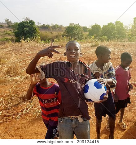 BAMAKO MALI - MAR 25 2017: Happy African children with soccer football ball playing on red dusty streets of Bamako Mali