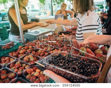 STRASBOURG FRANCE - JUN 25 2017: Customer waiting to pay for organic delicious strawberries and black currant at an open-air Saturday market in Strasbourg