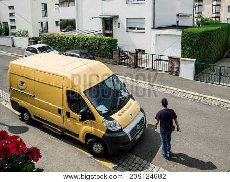 PARIS FRANCE - JUN 23 2017: Courier walking toward La Poste yellow delivery van for the delivery on time package parcel - aerial view