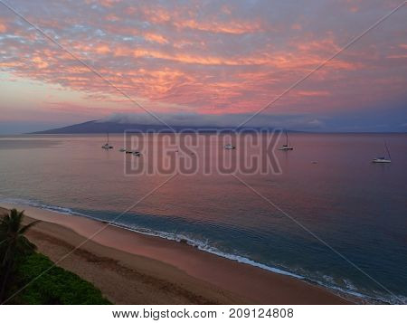 Pink Morning Sunrise Over Hawaii Beach with Bright Colored Clouds Reflecting over Vast Ocean and Island in Distance