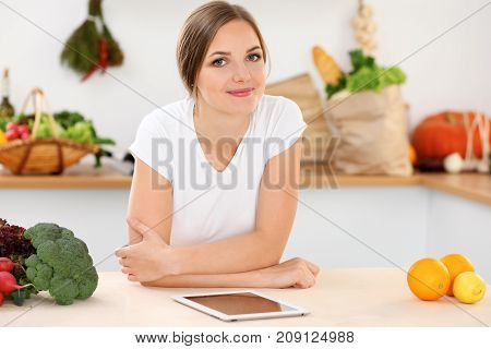 Young woman is making online shopping by tablet computer and credit card. Housewife found new recipe for cooking in a kitchen.