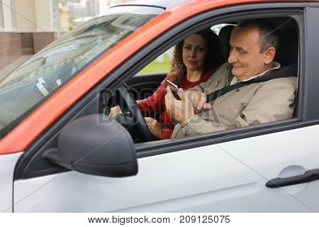 Woman and man with smartphone fastened with seat belts sit in car, focus on man