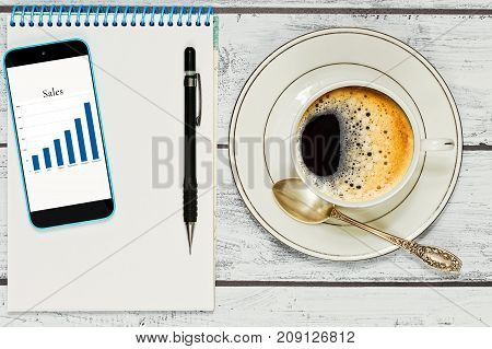 Having coffee while making some time managment activity with notepad and pen and checking the sales report on smartphone screen. Time management and organizing concept. Top view.