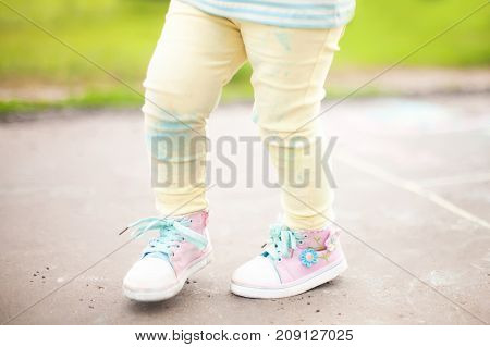 Little girls stained pants after drawing wirh color chalk summer and happy childhood concept.