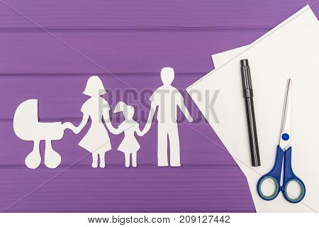The silhouettes cut out of paper of man and woman with child and pram, scissors and marker near on a white sheet of paper on purple wooden background. Concept of family love