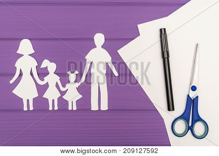 The silhouettes cut out of paper of man and woman with two girls, scissors and marker near on a white sheet of paper on purple wooden background. Concept of family love