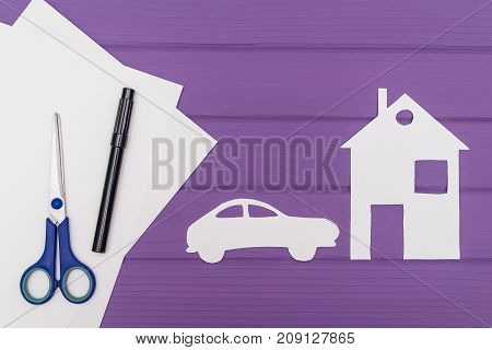 The silhouettes cut out of paper of car and house, scissors and marker near on a white sheet of paper on purple wooden background, car insurance concept