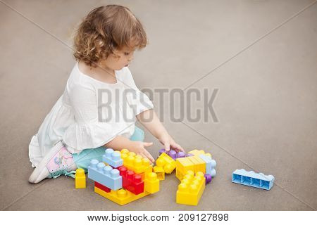 Adorable little girl play with color plastic block building and having fun. Playing with educational toys. Early building and having fun. Playing with educational toys. Early developement. Empty place for text.