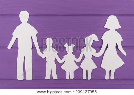 The silhouettes cut out of paper of man and woman with two girls and boy on purple wooden background. Concept of family love