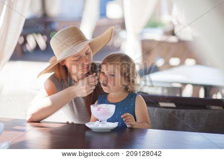 FMoher feeding llittle girl with ice cream indoors. Family lifestyle.