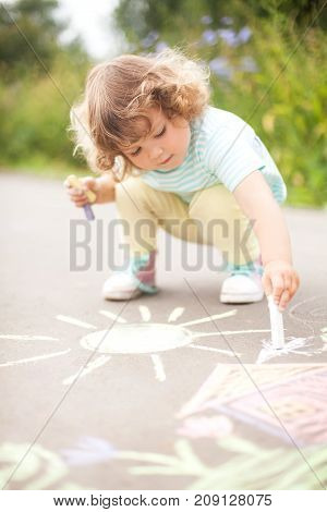 Sunny and warm summer days and happy chilhood. Cute curl hair blond little girl drawing with chalk crayons at the asphalt. Kid's drawings: sun home and flowers.